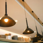 Vintage industrial lamps hanging from the ceiling in a cafe